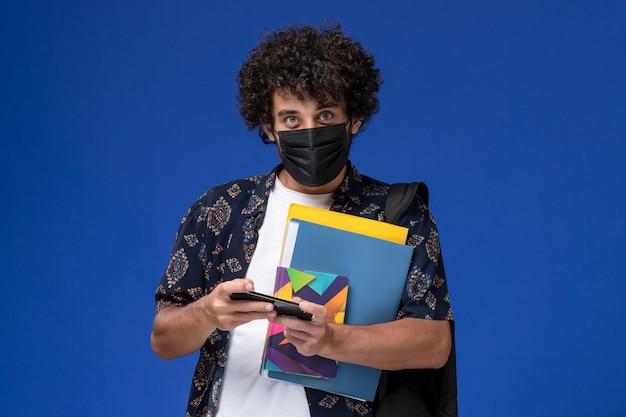 Vista frontale giovane studente maschio che indossa la maschera nera con zaino che tiene i file e utilizzando il suo telefono su sfondo blu.