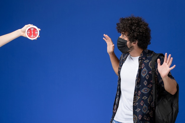 Vista frontale giovane studente maschio che indossa una maschera nera con zaino paura degli orologi sullo sfondo azzurro. Foto Gratuite