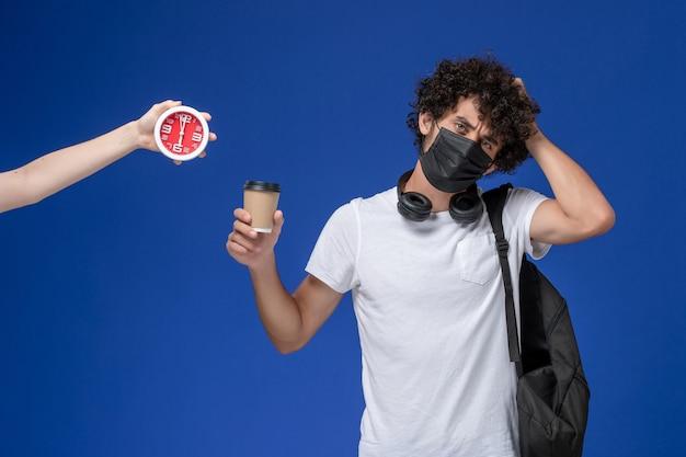 Giovane studente maschio di vista frontale in maglietta bianca che porta maschera nera e che tiene tazza di caffè sui precedenti blu.