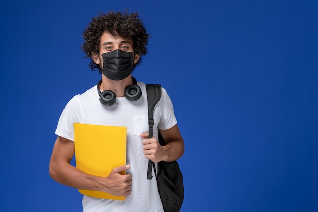Front view young male student in white t-shirt wearing black mask and holding yellow files on light-blue background.