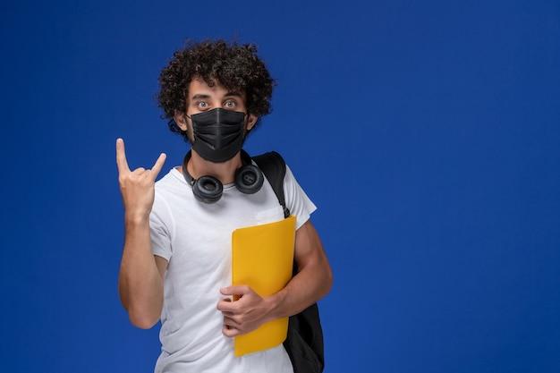 Giovane studente maschio di vista frontale in maglietta bianca che porta maschera nera e che tiene file gialli su sfondo azzurro.
