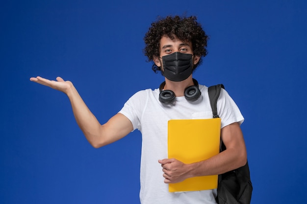 Front view young male student in white t-shirt wearing black mask and holding yellow files on the light blue background.