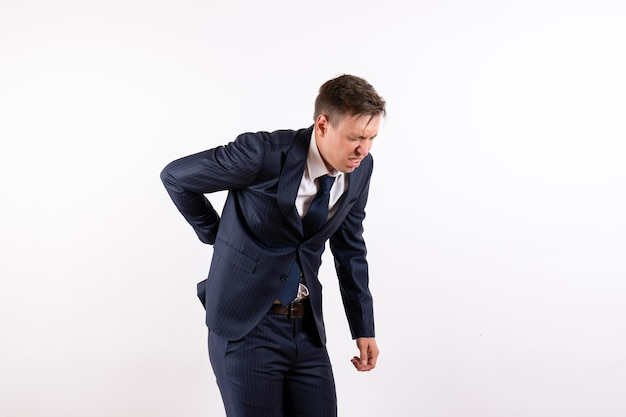Front view young male suffering from back ache in classic strict suit on white background