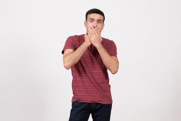 Vista frontale giovane maschio in t-shirt in posa con espressione scioccata su sfondo bianco