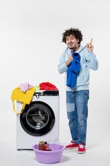 Vista frontale del giovane maschio che tira fuori i vestiti puliti dalla lavatrice sul muro bianco