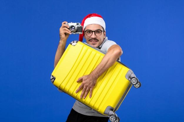 파란색 벽 비행 휴가 비행기에 카메라와 함께 전면보기 젊은 남성 복용 사진