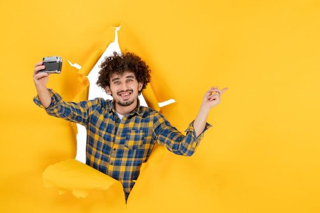 前视图年轻男性用黄色背景的相机拍照