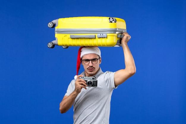 Вид спереди молодой мужчина фотографирует и держит сумку на синей стене в отпуске полета самолета