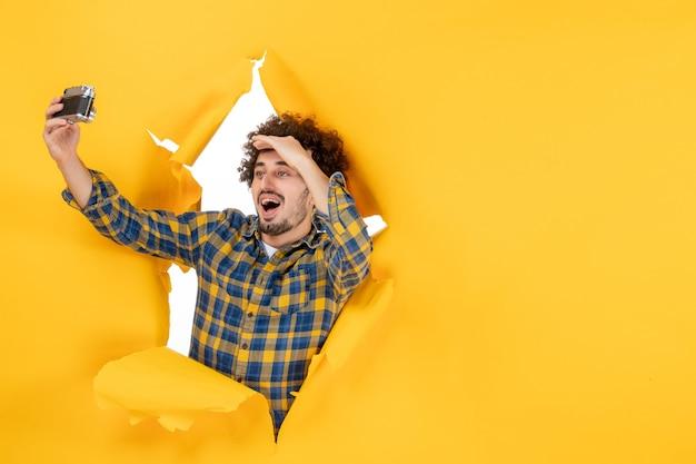 黄色の背景にカメラでselfie写真を撮る正面図若い男性