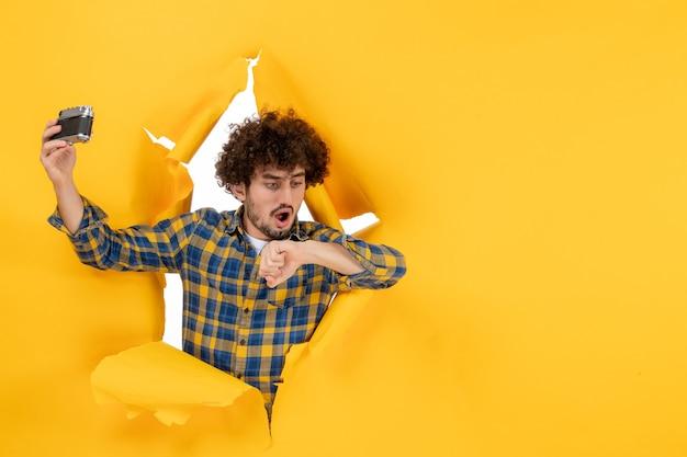 노란색 바탕에 카메라와 함께 selfie 사진을 복용 전면보기 젊은 남성