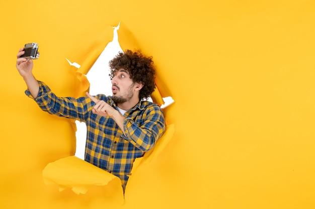 正面图:年轻男性在黄色背景下用相机自拍