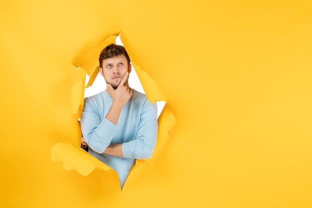 Вид спереди молодой мужчина думает на желтом разорванном фоне