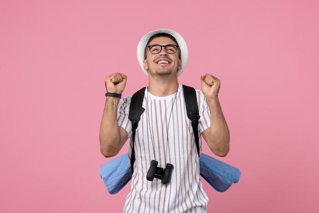 Vista frontale giovane turista maschio in maglietta bianca su sfondo rosa