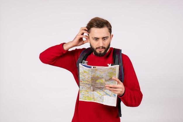 Вид спереди молодой турист-мужчина с рюкзаком, изучающий карту на белой стене, самолет covid, отпуск, эмоция, вирус, цвет полета