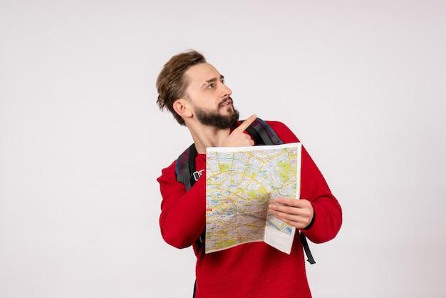 Вид спереди молодой мужчина-турист с рюкзаком, изучающий карту на белой стене, самолет, город, отпуск, эмоция, человеческий цвет, туристический маршрут
