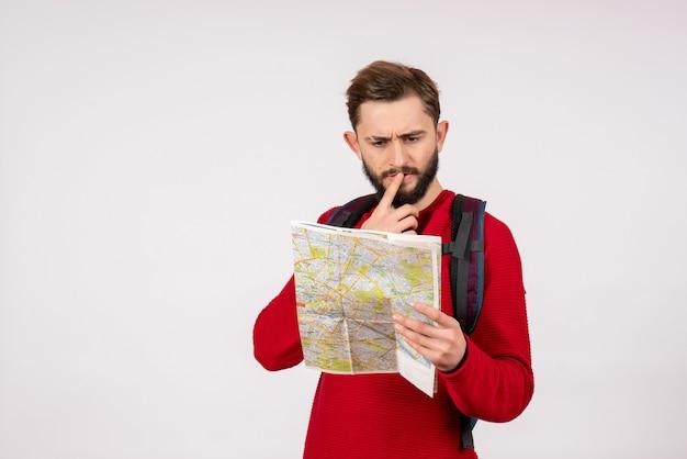 Вид спереди молодого мужчины-туриста с рюкзаком, изучающего карту на белой стене, городские каникулы, эмоции, человеческий цвет, туристический маршрут