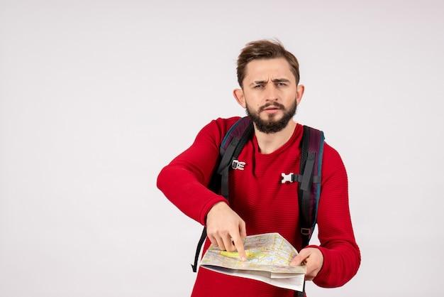 Вид спереди молодой мужчина-турист с рюкзаком, изучающий карту на белой стене, человеческий город, отпуск, эмоция, цвет, туристический маршрут