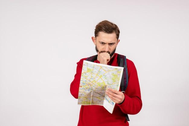 Вид спереди молодого мужчины-туриста с рюкзаком, изучающего карту на белой стене самолета, городские каникулы, эмоции, цвет, туристический маршрут