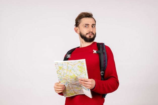 Вид спереди молодой турист-мужчина с рюкзаком, изучающий карту на белой стене, самолет, город, отпуск, эмоция, человеческий цвет, маршрут