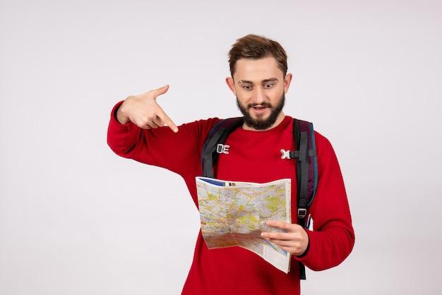 Вид спереди молодой турист-мужчина с рюкзаком, исследующий карту на белой стене, самолет, город, отпуск, эмоция, человеческий цвет, туризм