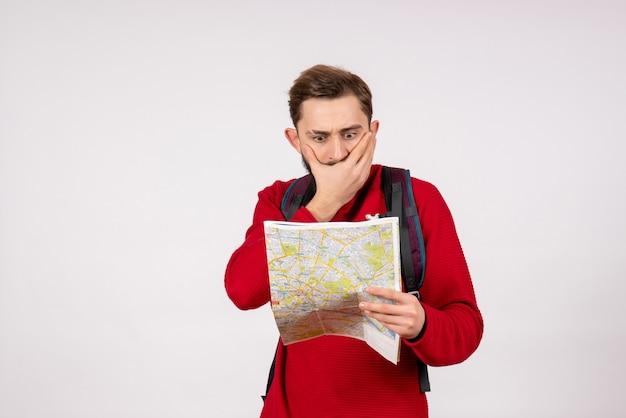 Вид спереди молодой мужчина-турист с рюкзаком, изучающий карту на белой стене, самолет, город, отдых, эмоции, человеческий цвет, туризм