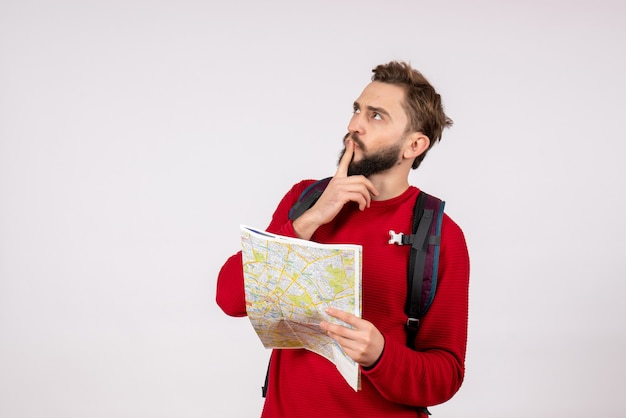 Вид спереди молодой мужчина-турист с рюкзаком изучает карту, думая на белой стене, самолет, город, отпуск, эмоция, человеческий цвет, туризм