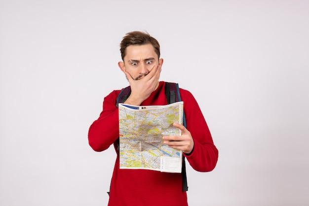 Giovane turista maschio di vista frontale con lo zaino che esplora la mappa sul colore di volo del virus di emozione di vacanza di aereo di covid della parete bianca