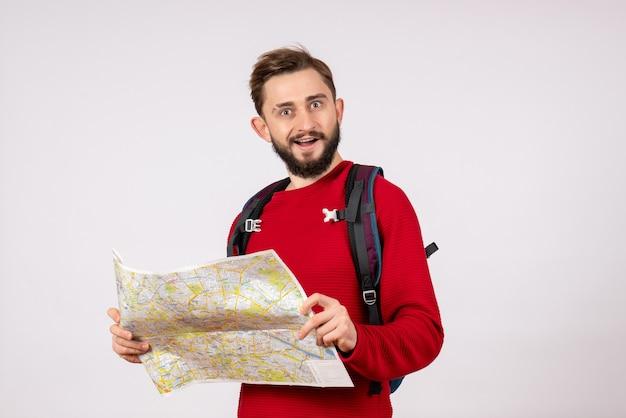 Giovane turista maschio di vista frontale con lo zaino che esplora la mappa sul colore di volo del virus delle emozioni di vacanza dell'aereo covid della parete bianca