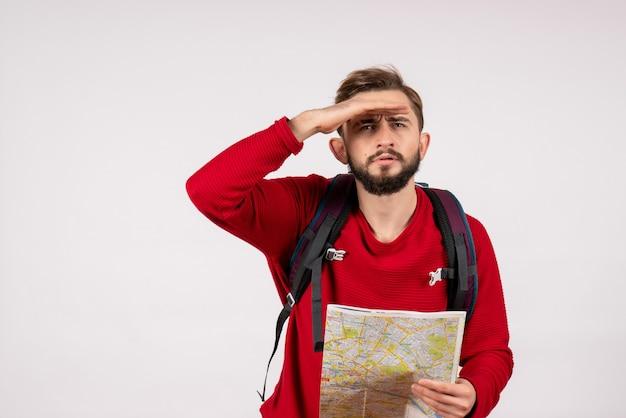 Vista frontale giovane turista maschio con lo zaino esplorando la mappa sul percorso del turismo di colore umano di città aereo muro bianco emozione