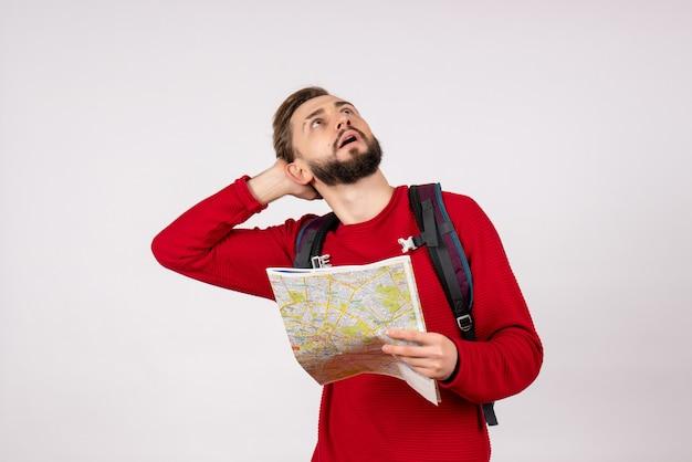 Vista frontale giovane turista maschio con zaino esplorando la mappa sul turismo di colore umano di colore umano di viaggio aereo città vacanza emozione
