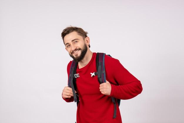 白い壁に笑みを浮かべてバックパックと若い男性の観光客の正面図
