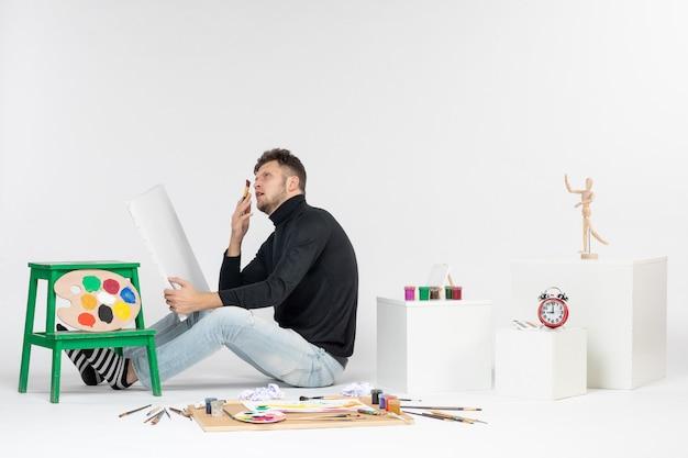 白い壁にタッセルで絵を描くことを試みている正面図若い男性写真ペイントアートカラーペイント描画アーティスト