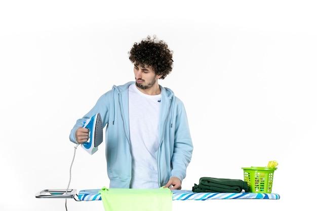 전면보기 젊은 남성 배경에 수건을 다림질하려고합니다 철 색 남자 세탁 옷 가사 청소 감정