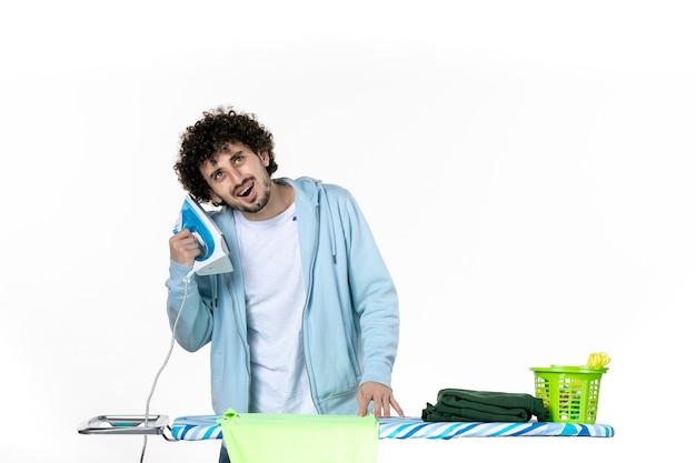 전면보기 젊은 남성 흰색 배경에 철을 들으려고 노력하는 철 색 남자 청소 가사 세탁 사진 옷