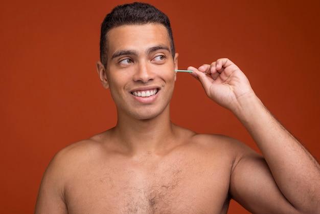 Giovane maschio di vista frontale usando i bastoncini dell'orecchio