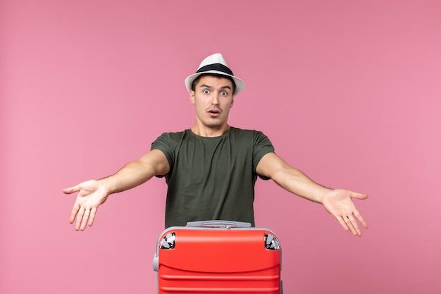 Vista frontale giovane maschio in vacanza che porta borsa rossa su spazio rosa chiaro light
