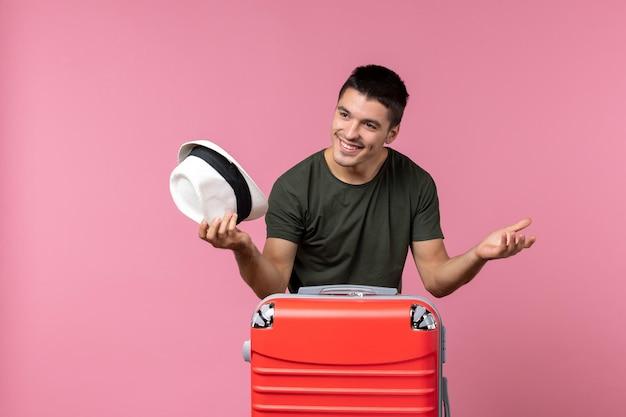 Vista frontale giovane maschio in vacanza tenendo il cappello e salutando qualcuno sullo spazio rosa