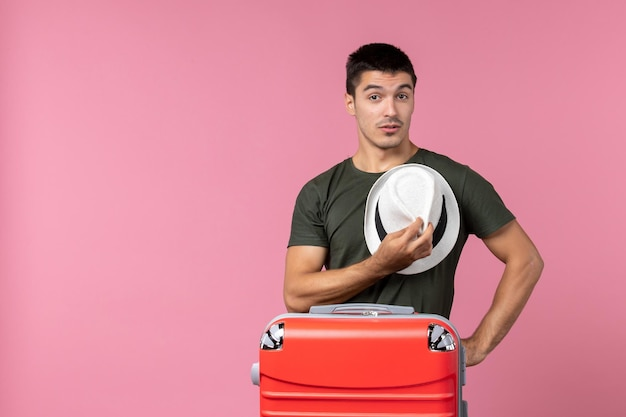Vista frontale giovane maschio in vacanza con cappello su spazio rosa