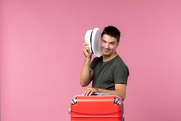 Vista frontale giovane maschio in vacanza che tiene il cappello e nasconde la faccia su uno spazio rosa