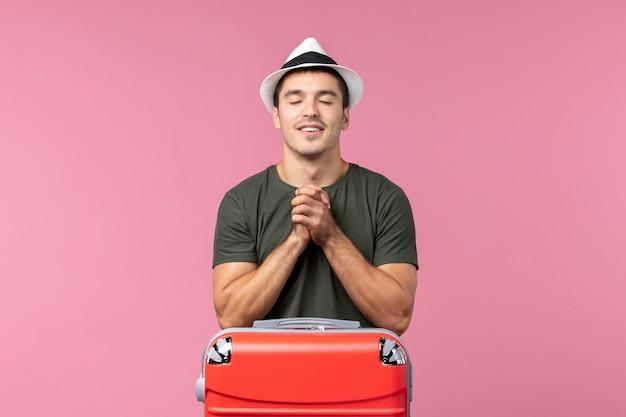 Vista frontale giovane maschio in vacanza che tiene il cappello sullo spazio rosa