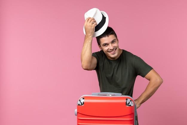 Vista frontale giovane maschio in vacanza che indossa cappello e sorride sullo spazio rosa