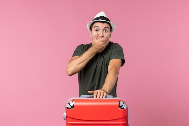 Vista frontale giovane maschio in vacanza con big bag scioccato sullo spazio rosa