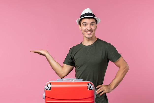 Giovane maschio di vista frontale in vacanza con la grande borsa che sorride sullo spazio rosa