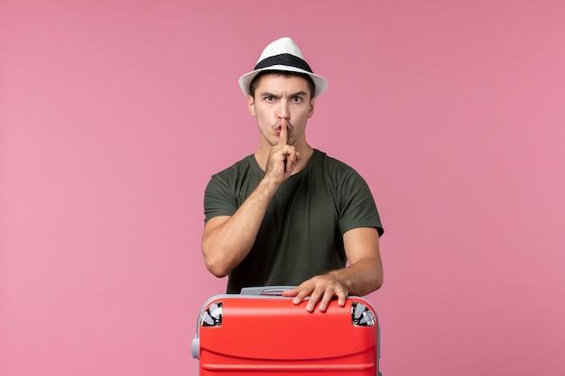 Vista frontale giovane maschio in vacanza con borsa rossa sullo spazio rosa