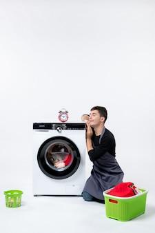Vista frontale del giovane maschio in attesa fino alla fine del lavaggio dei vestiti sul muro bianco