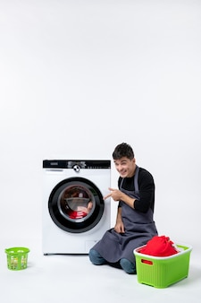 Front view of young male washing clothes with the help of washing machine on a white wall