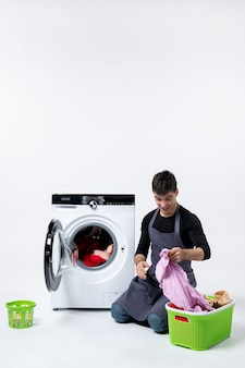 Front view of young male washing clothes with the help of washing machine on the white wall
