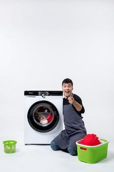 Vista frontale del giovane maschio che lava i vestiti con l'aiuto della lavatrice sul muro bianco
