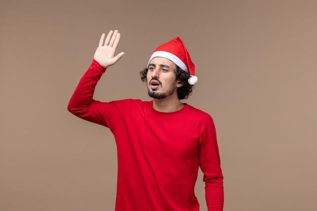 正面図茶色の背景の感情のクリスマス休暇に手を振っている若い男性