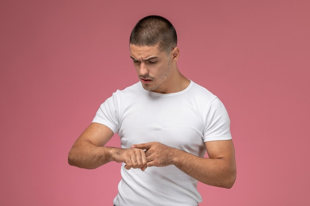 Front view young male in white shirt looking at his wrist on the pink background